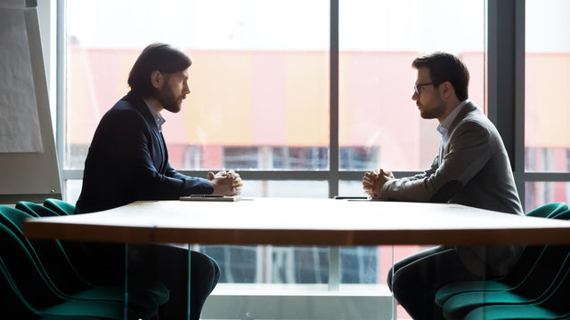 Two businessmen sitting opposite at table, confrontation and negotiation