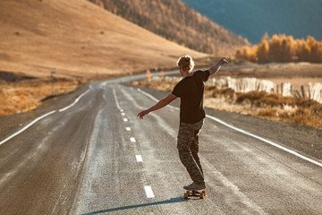 Lonely skateboarder on longboard at mountain road