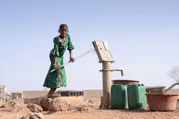 Happy Aboriginal Young Girl with lots of Water in a village