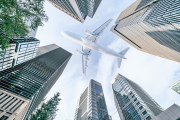 Poster Airplane Aircraft flying above glass office buildings in the sky over city buildings in financial district of Tokyo city, Japan