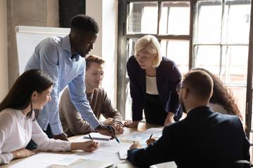Diverse staff engaged at financial stats information analysis at meeting