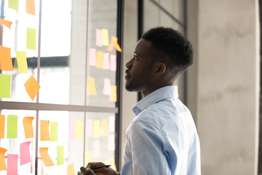 African businessman creates to-do list attaching post-it notes