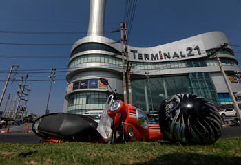 A motorcycle and helmet that belongs to a victim lie in front of the Terminal 21 shopping mall following a gun battle involving a Thai soldier on a shooting rampage, in Nakhon Ratchasima