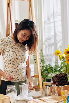 Smiling young Asian woman mixing ingredients when making soap bars or bath bombs at home
