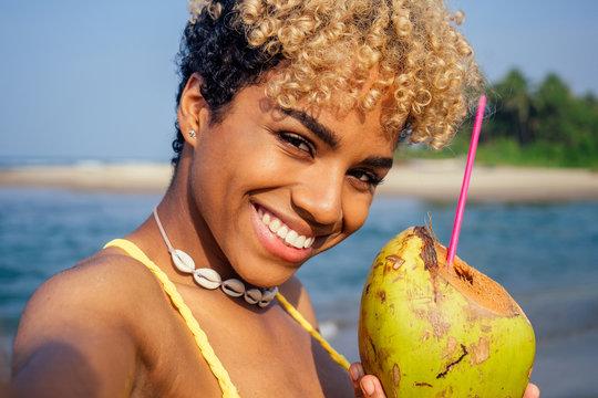 hispanic latin beautiful female drinking coco nut water seashells on the neck and taking selfie on camera phone