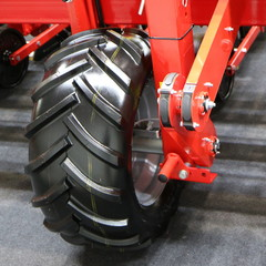 Red metal support with a large wheel.