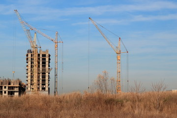 Tower cranes are working on the construction of a new house. Lifting crane.