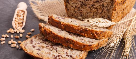 Fresh wholegrain bread for breakfast and ears of rye or wheat grain