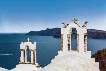 The bell towers of Greek Orthodox Church on the background waters of the Aegean sea in Oia town on Santorini island in Greece