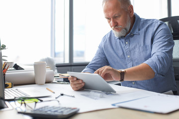 Mature businessman working using digital tablet while sitting in the modern office.