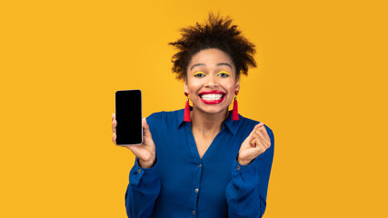 Wall Mural - Afro girl showing blank black cellphone screen
