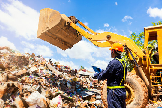 Crane operator. The engineer is controlling the loader to get the iron to recycle. Worker standing in metal landfill outdoors.