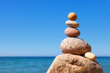 Rock zen pyramid of white and pink pebbles on a background of blue sky and sea.