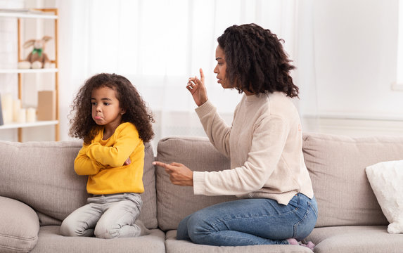 Black Mother Scolding Daughter Sitting On Sofa At Home
