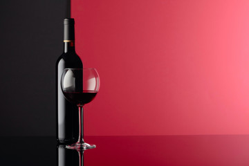 Glass and bottle of red wine on a black reflective background. Copy space.