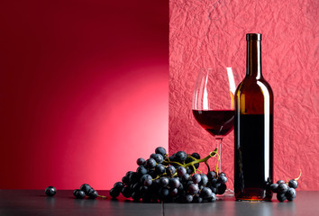 Bottle and glass of red wine on a black table. Fototapete