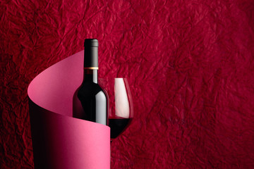 Bottle of red wine on a red background. Copy space.