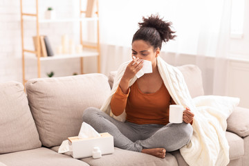 Sick Afro Woman Blowing Nose In Tissue Sitting On Sofa