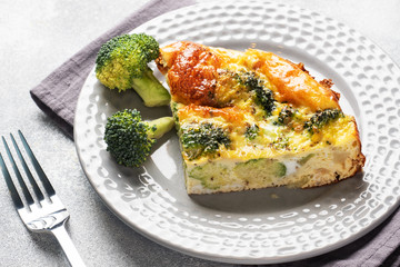 Piece Baked omelet with broccoli on a plate. Concrete table. Healthy diet food dish.
