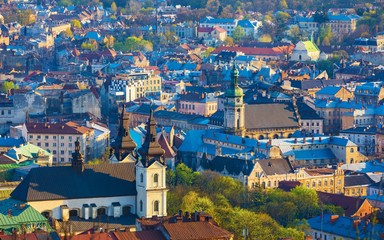 Aerial sunset view of historical old city district with churches, cathedrals and houses roofs in Lviv, Ukraine.