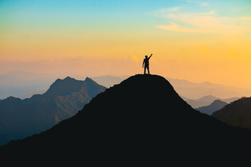 The silhouette of a man with a cheerful raise in his hand on the top of the mountain During sunset time The concept of effort and success