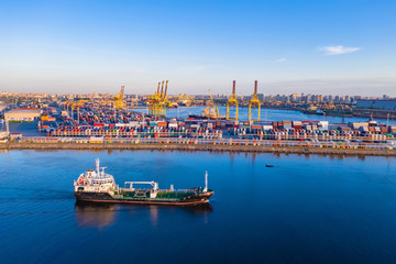 Cargo ship is on the fairway. Sea commercial port. On the pier are containers with goods. Cranes carry out loading and unloading. Transportation of goods by sea. Panorama of the port.