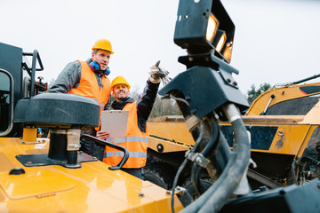 Fotomurales - Two male workers on excavator in digging operation or quarry