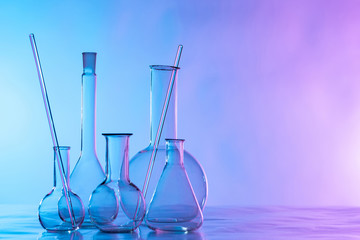 Chemical glassware is on the table. Flasks and test tubes on a lilac background. Chemical laboratory equipment. Dishes for demonstration of chemical reactions