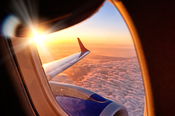 plane wing from airplane window seat in flight nature landscape against scenic sunset sky background. Aerial view from aircraft passenger cabin on beautiful red orange sunrise cloudscape and blue sky