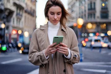 Young woman with smartphone on night street