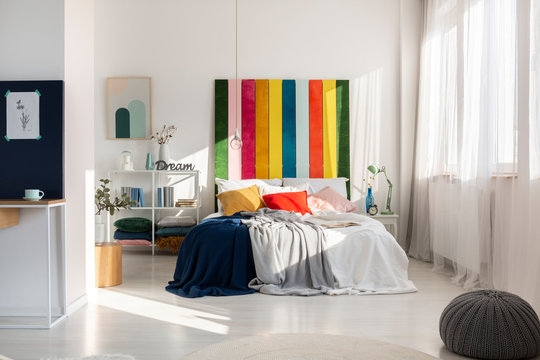Colorful bedroom interior with rainbow colored bedhead