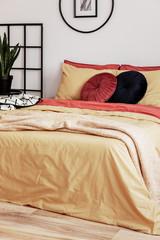 Black round velvet pillow on yellow duvet in trendy bedroom interior with king size bed