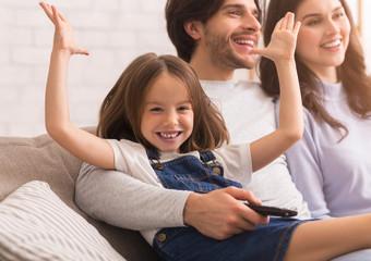 Joyful Little Girl Raising Hands And Smiling Next To Parents