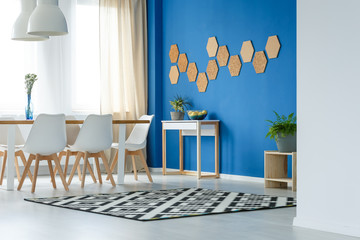Cork honeycombs on blue wall of trendsetting dining room interior with patterned carpet, plants and white furniture