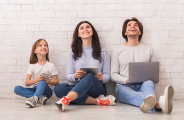 Family Sitting On Floor With Diverse Gadgets And Looking Upwards
