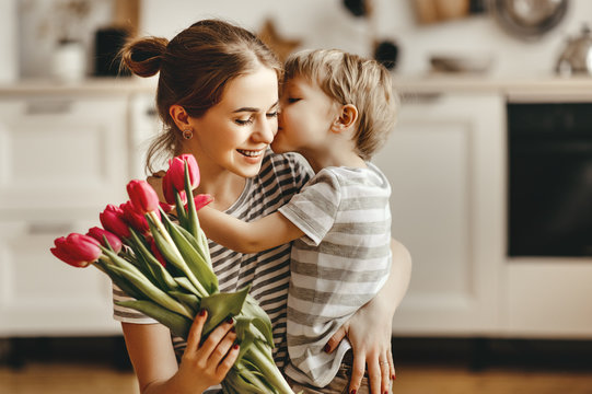 happy mother's day! child son gives flowers for  mother on holiday