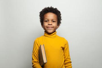 Cute African American kid boy student holding book on white background. Black kid school boy portrait Fototapete