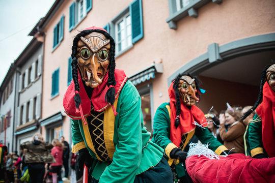 Freiburger Hexen - Hexen mit Katzenaugen veranstalten ein Konfettibad und suchen Opfer. Bei Fastnachtsumzug in Staufen Süd Deutschland.