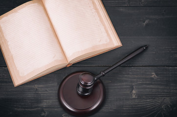 Judge Gavel and law book on a black wooden background, law library concept.