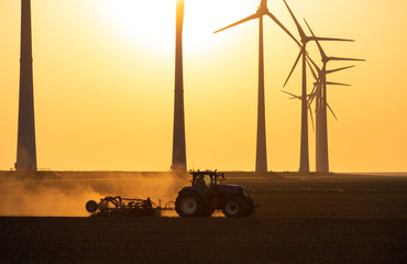 A tractor cultivating farmland during sunset at a row of windturbines. Groningen, Holland.