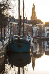 GRONINGEN - NETHERLANDS, December 19, 2019:  Ships and boats in a canal in Groningen during a tranquil, winter sunrise.