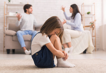 Family Conflict. Little girl crying after parents quarrel at home