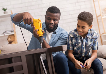 Black father teaching his son how to use drill perforator