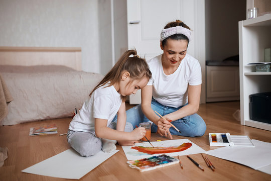 woman and attractive cute kid learning to colour rainbow, learning colours. close up photo. girl going to be a painter, artist, talent concept