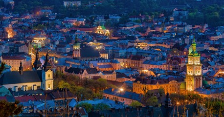 Aerial night view of historical old city district with churches, cathedrals and houses roofs in Lviv, Ukraine.