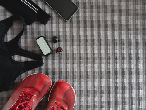 top view sport wear concept with Gym Outfit, running shoes, smartphone, true wireless earbuds and sport run accessories on white background.