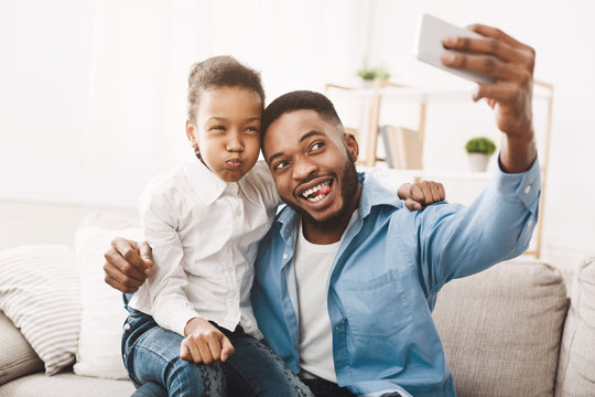 Happy afro father taking selfie with his funny daughter