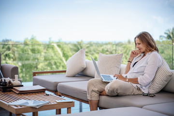 Attractive woman 40 years old in a white shirt sitting on a gray sofa working on a laptop on the terrace overlooking the green jungle on a bright sunny day