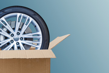 Open Cardboard Box with Tires on blue background. Online store of auto parts.