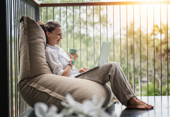 Happy beautiful young woman in a white shirt sits an  bean bag chair working on a laptop on the terrace overlooking the green jungle on a bright sunny day